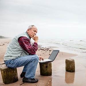 Man sitting on a breakwater bollard on a dull day