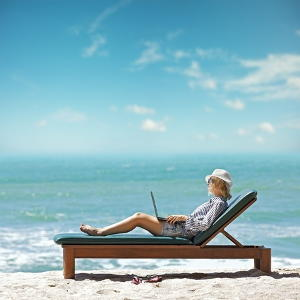 Woman on a beach with a laptop
